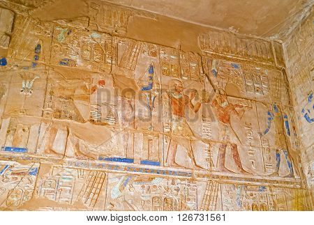 LUXOR EGYPT - OCTOBER 7 2014: The reliefs depict the traditional for Egyptian Temples scenes of Pharaohs' life and mythology on October 7 in Luxor.