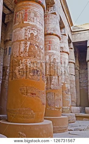 The ancient columns of the Peristyle Court of the Khonsu Temple covered with covered with the reliefs and remains of murals Karnak Complex Luxor Egypt.