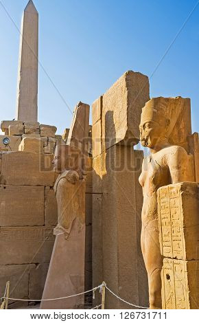 The ancient statues at the entrance to the ruined temple with the Hatshepsut Obelisk on the background Karnak Complex Luxor Egypt.