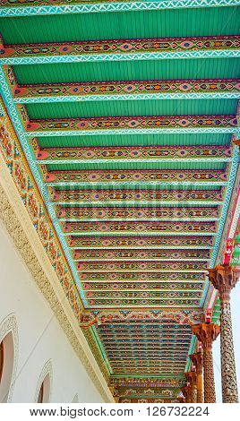 KOKAND UZBEKISTAN - MAY 6 2015: The wooden canopy of the Jami Mosque with colorful islamic patterns and carved capitals of the wooden pillars on May 6 in Kokand.