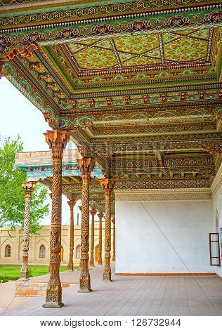 KOKAND UZBEKISTAN - MAY 6 2015: The wooden canopy in the courtyard of the Jami Mosque covered with colorful arabesques on May 6 in Kokand.