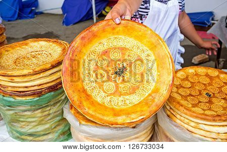 The Uzbek bakers decorate the lochira flat bread with the interesting patterns made with the special chakich stampers Pungan Uzbekistan.