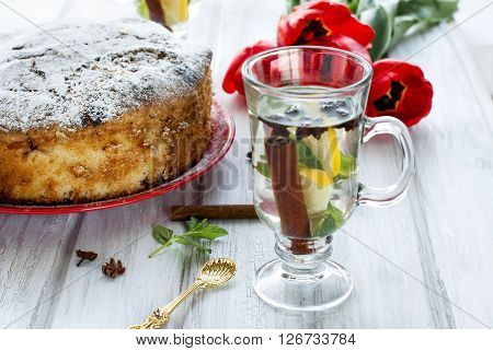 Home-made Cake With Fruit And Fragrant Tea With Lemon, Cinnamon And Mint In A Tall Glass Goblets