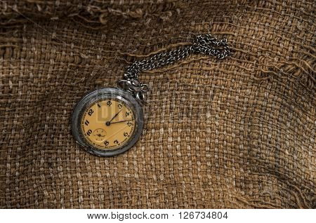 Old pocket watch on a textured vintage background