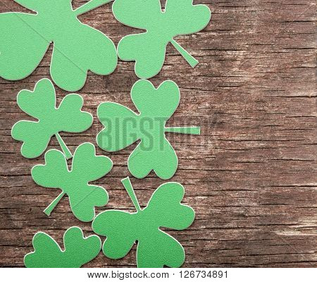 Green clovers or shamrocks on rustic wood background