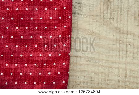 Red polka dot tablecloth or towel over the surface of a wooden table