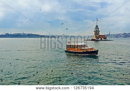 The pleasure boat next to the Maiden's Tower on Bosphorus Istanbul Turkey.