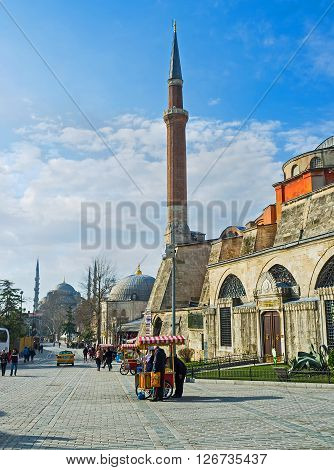 ISTANBUL TURKEY - JANUARY 21 2015: The side wall of the Hagia Sophia Museum with the high minaret and the silhouette of the slender minaret of the Blue Mosque on the background on January 21 in Istanbul.