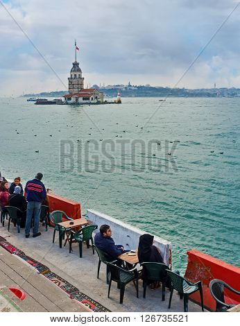 ISTANBUL TURKEY - JANUARY 21 2015: The outdoor teahouse on the Uskudar embankment is the best place to relax with a view on the Maiden's Tower on January 21 in Istanbul.
