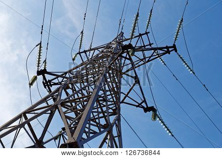High voltage tower. Electricity transmission pylon on a background of blue sky