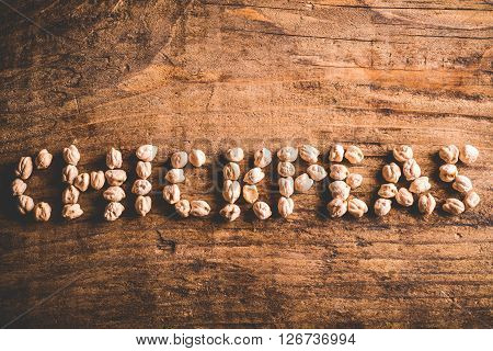 chickpeas written with chickpeas on wood background
