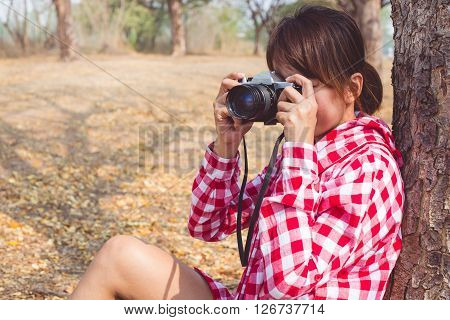 Tourist young woman holding vintage old photo camera take a photo in outdoor