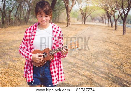 Beautiful asian women playing ukulele guitar at outdoor