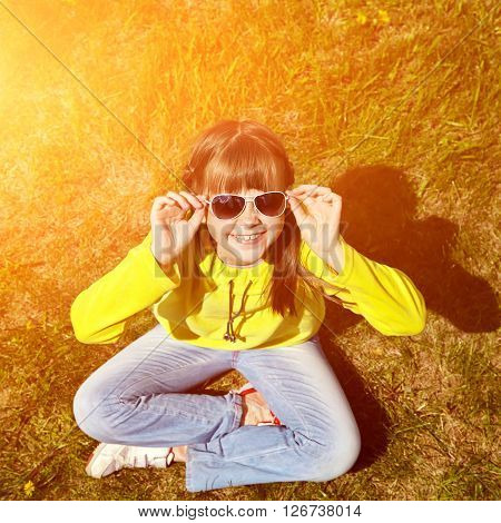 stylish girl in sunglasses sitting on the grass in the park. children outdoors. vacation in the summer park
