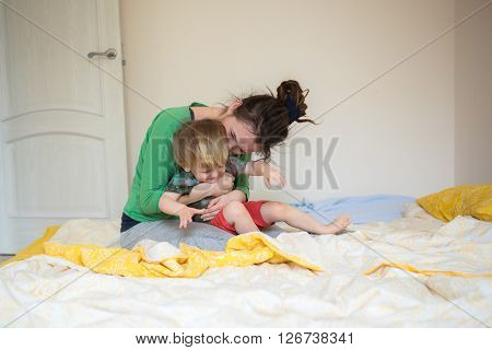 Closeup of happy family playing over the bed in a relaxed morning. Weekend family leisure time concept. real interior casual lifestyle mom and son embrace