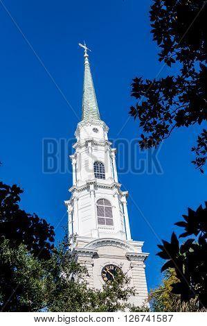 A white church steeple against a clear blue sky