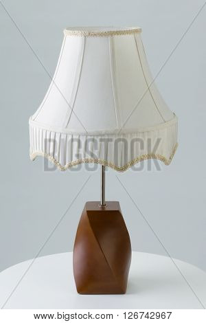 Table lamp on end table against gray background