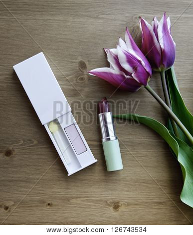 Tulips, lipstick and eye shadows. Two purple tulips and cosmetics on wooden background. Small bouquet of tulips. Cosmetics and flowers. Two violet tulips with white margins.