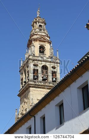 Bell tower of the mosque of Cordoba between the facades of the houses - Spain.