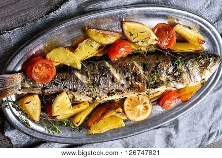 Grilled fish with potato wedges top view country style