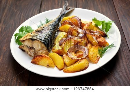 Baked potato wedges and mackerel fish on white plate
