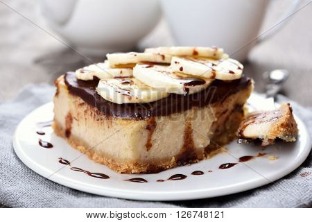 Cheese cake with chocolate syrup and piece of banana close up