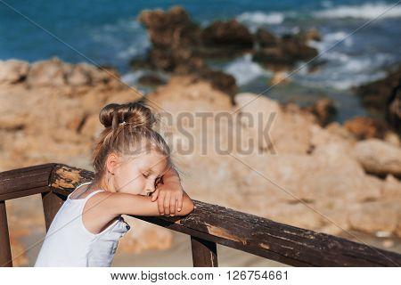 Beautiful girl posing on the seashore with eyes shut
