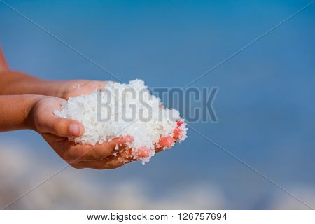 Female hands with sea salt for spa from Dead Sea. Israel