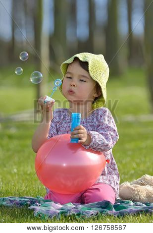 little girl with soap bubbles having fun outdoors