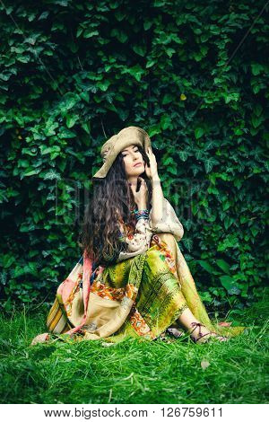 young woman in silky boho style dress and and hat sit in garden summer day full body shot