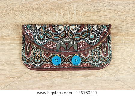 female purse money artist's design with two wooden buttons on wood background, handmade floral paisley pattern