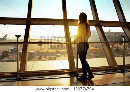 Woman standing at airport with morning sunlight