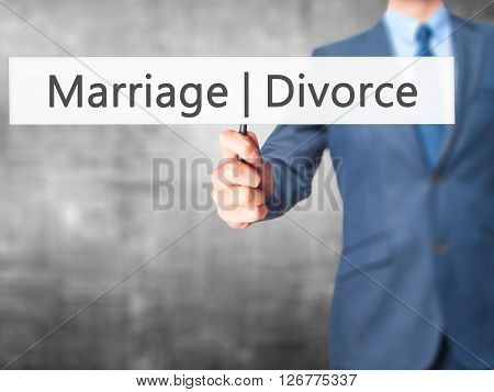 Marriage  Divorce - Businessman Hand Holding Sign