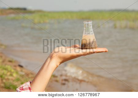 Water Purity Test. Hand holding a chemical flask with water, lake or river in the background.