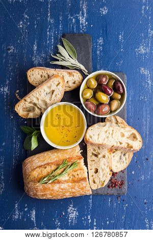 Mediterranean snacks set. Olives, oil, herbs and sliced ciabatta bread on black slate stone board over painted dark blue background, top view.