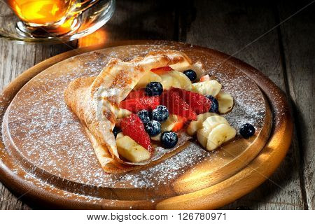 view of nice fresh hot crepes with berries   on color background