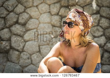 Fashion portrait of middle age hipster woman with turban and sunglasses near the stone wall