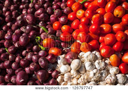 Colourful pile of red Roma tomatoes, purple Spanish onions and white garlic at an outdoor vegetable market in Thimphu, Bhutan
