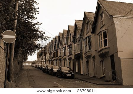 street view of houses on a steep hill in cobh county cork ireland in sepia