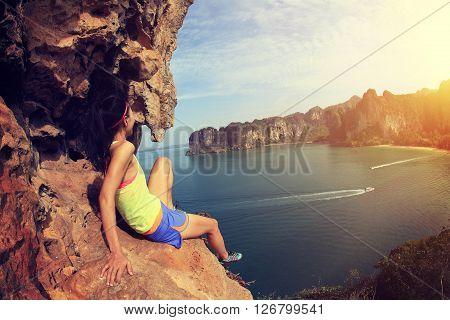 young woman rock climber at seaside mountain rock