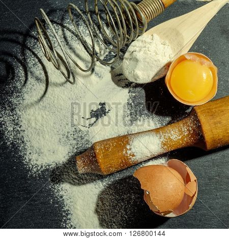 Dough preparation. Baking ingredients: egg and flour on the graphite board.