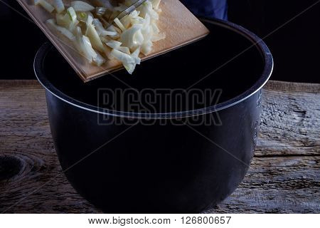 Onions circles, green onion with on board on wooden background