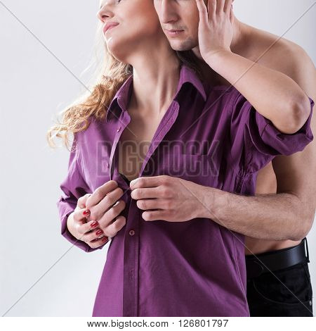 Man unbuttoning  young woman's shirt before sex