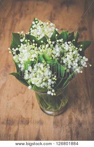 Home decor, lilies of the valley in a vase on a rustic table, vintage style