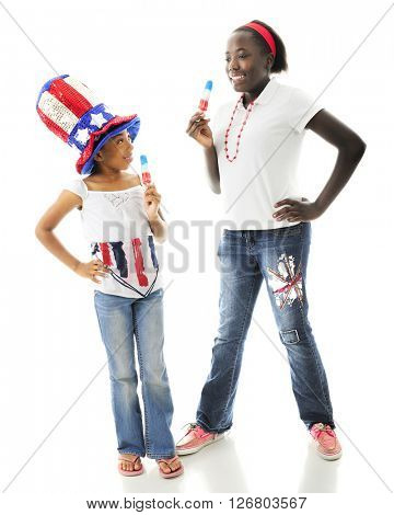 Two African American sisters enjoying tri-colored Popsicles together while wearing their country's colors.  On a white background.