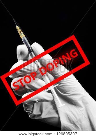 Stop doping concept. Hand in glove with syringe isolated on black