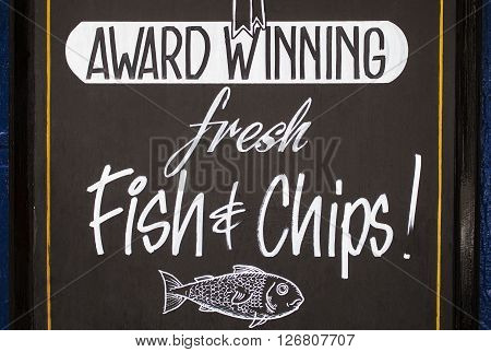 A board outside a vintage pub advertising fresh Fish and Chips - a traditional British meal.