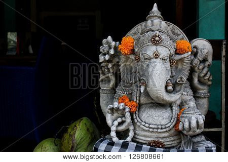 Bali people pray to Ganesha with flower and coconut