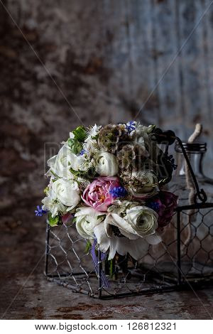 Bouquet from pink tulips violet grape hyacinths white anemones violet veronica and white buttercup with violet ribbon lying in the metal basket with glass bottle on rought metal background with rust
