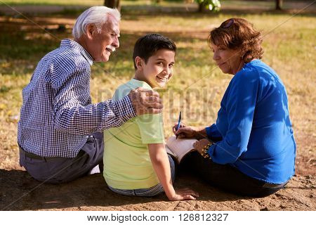Grandparents educating grandson: Senior woman and old man spending time with their grandchild in park. The old people help the boy studying and doing school homework. The kid looks at camera smiling